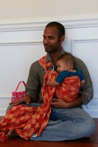 Daddy wears his daughter in a Ring Sling