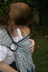 Holly, a Bay Area Volunteer Babywearing Educator nursing in a cradle hold with a Ring Sling