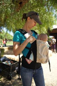 Sarah, a Volunteer Babywearing Educator demonstrates one-handed nursing in an Ergo