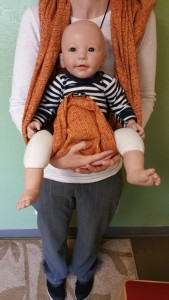 """Pulling the fabric up to the Baby's belly button or tucking it into their diaper, a hack often referred to as """"The Pant Trick"""""""